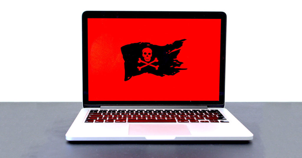 Laptop computer with the skull and crossbones flag on a red background.